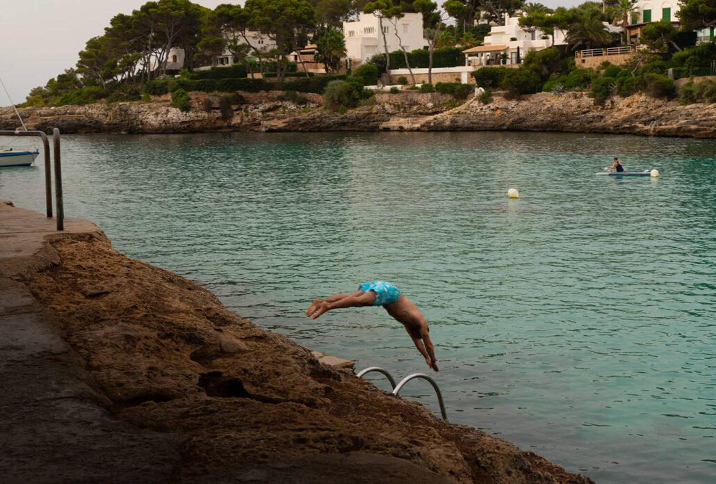 Hombre nadando a primera hora en Cala Gran